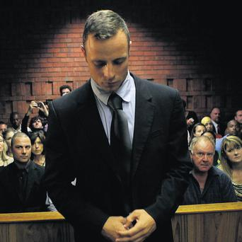 Oscar Pistorius in Pretoria magistrate's court. On the right is his coach, Ampie Louw, and on the left is his brother, Carl.