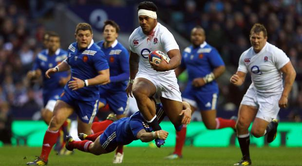 England's Manu Tuilagi (C) runs with the ball during their Six Nations rugby match against France