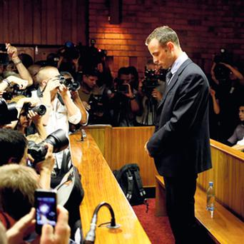 ACCUSED OF MURDER: Oscar Pistorius in the dock of a Pretoria magistrates court. After being released on bail on Friday the Paralympic gold medallist told his uncle that the 'family of Reeva is on his mind all the time'.