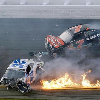 Kyle Larson's car is on fire as he slides down the track with Regan Smith after being involved in a crash at the conclusion of the NASCAR Nationwide Series auto race in Daytona Beach, Fla. Larson's car hit the safety fence sending car parts and other debris flying into the stands injuring spectators.