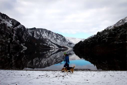 Ray Barrar, from Hollywood, Co Wicklow, and his dog walk by the snow-covered shore of the upper lake in Glendalough, Co Wicklow, yesterday