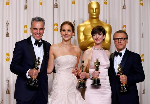 Daniel Day Lewis (L), Jennifer Lawrence, Anne Hathaway, and Christoph Waltz, pose with their Oscars backstage at the 85th Academy Awards