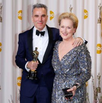 Daniel Day-Lewis (L) poses with presenter Meryl Streep after receiving his Oscar for Performance By An Actor In A Leading Role for