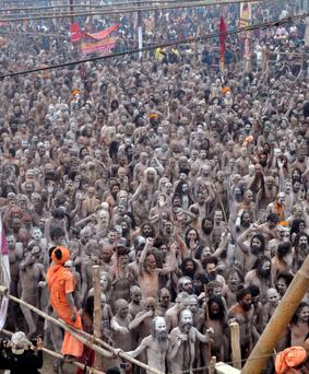 Naga Sadhus or Hindu holy men raise their arms while shouting religious hymns on the banks of the river Ganges