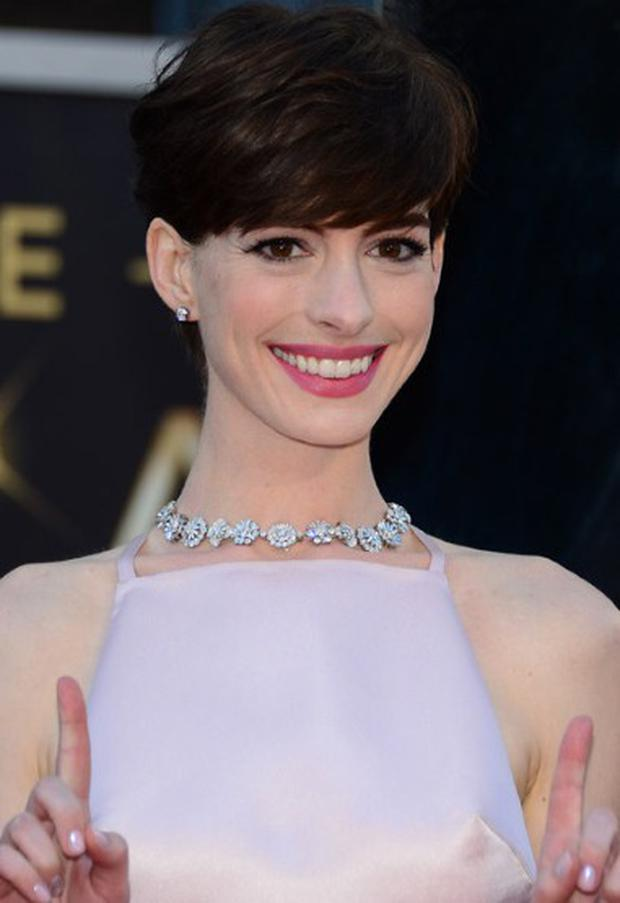 Anne Hathaway continues to think pink, and ditches her signature red lipstick, for a, we think, far more flattering look on her pale rose complexion. Matched with her softer blow-out too, it just works.