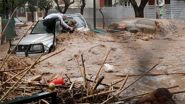 A woman is rescued from flood waters by a resident standing on top of her car during heavy rain in the Chalandri suburb north of Athens