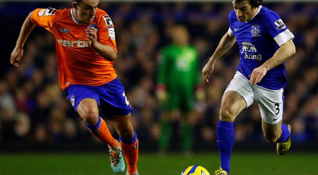 Everton's Leighton Baines (R) runs past Oldham Athletic's Kirk Millar during their FA Cup fifth round replay soccer match at Goodison Park