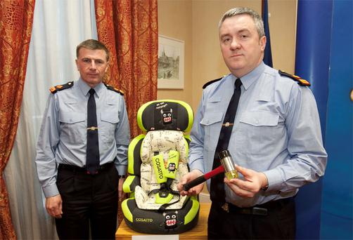 Gda Supt Gerard Curley (left) and David Taylor, from the Garda Press Office, with replicas of the hammer found at the crime scene and the child's seat that was in the getaway car used in the murder of Det Gda Adrian Donohoe