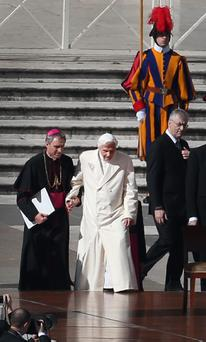 Pope Benedict XVI is helped onto the dias by his personal secretary Bishop Georg Gaenswein in St Peter's Square.