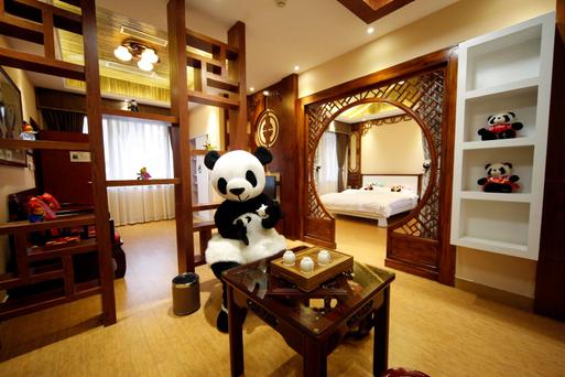 An employee dressed in a panda costume poses for a photo during the soft opening of a panda-themed hotel at the foot of Emei Mountain, in southwest China's Sichuan province