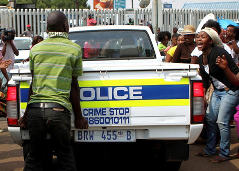 Protesters shout as a police vehicle drives into the Daveyton Police station east of Johannesburg February 28, 2013. South African police were caught on video dragging a man hundreds of metres from the back of a pick-up truck in the east Johannesburg area of Daveyton, hours before he died in custody, drawing a storm of protest against a force accused of routine brutality. The 27-year-old Mozambican taxi driver, Mido Macia, was found dead in detention with signs of head injuries and internal bleeding, according to an initial post mortem report released by the country's police watchdog. REUTERS/Stringer (SOUTH AFRICA - Tags: CRIME LAW SOCIETY) NO SALES. NO ARCHIVES. FOR EDITORIAL USE ONLY. NOT FOR SALE FOR MARKETING OR ADVERTISING CAMPAIGNS. SOUTH AFRICA OUT. NO COMMERCIAL OR EDITORIAL SALES IN SOUTH AFRICA