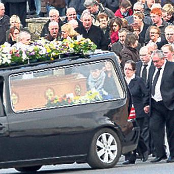 Friends and family follow the hearse at John Deegan's funeral.