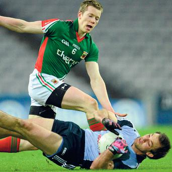 Dublin's Tomás Brady hits the ground under pressure from Mayo's Donal Vaughan.