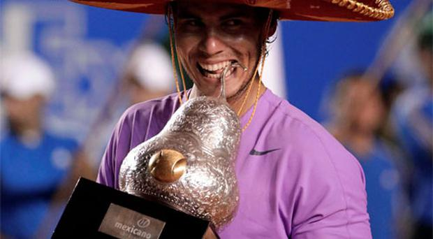 Rafael Nadal wearing a sombrero, poses with his trophy after defeating compatriot David Ferrer during their men's singles final match at the Acapulco International tennis tournament