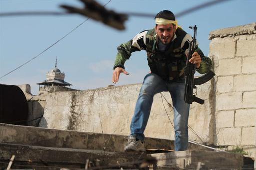 A member of the Free Syrian Army takes cover during clashes with forces loyal to Syria's President Bashar al-Assad, in the old city of Aleppo