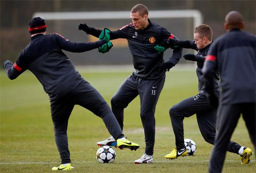 Manchester United's Tom Cleverley (L) and Wayne Rooney (R) challenge Nemanja Vidic during a training