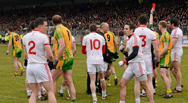 Referee Joe McQuillan, shows Michael Murphy, Donegal, hidden, a red Card at the end of the first half.