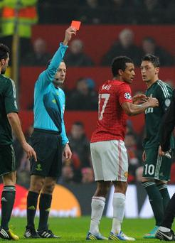 Manchester United's Nani receiving a red card from referee Cuneyt Cakir during the UEFA Champions League match at Old Trafford