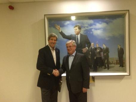 US secretary of state John Kerry poses for a photograph with Tánaiste Eamon Gilmore in front of a painting depicting President John F Kennedy's departure from Shannon following his 1963 visit to Ireland.
