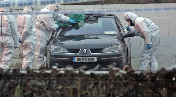 A forensics team examines bullet holes in a Renault Laguna after dissident republican Peter Butterly was shot in broad daylight
