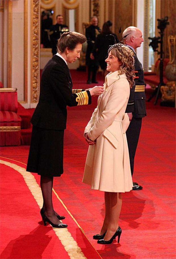 Charlotte Dujardin receives her OBE from Britain's Princess Anne wearing a coat by Paul Costelloe