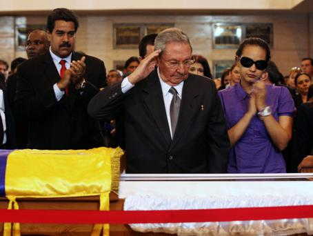 Cuba's President Raul Castro salutes the body of late Venezuelan President Hugo as he visits the wake with Chavez's daughter, Rosa Virginia (R), and Venezuela's Vice-President Nicolas Maduro (2nd L)