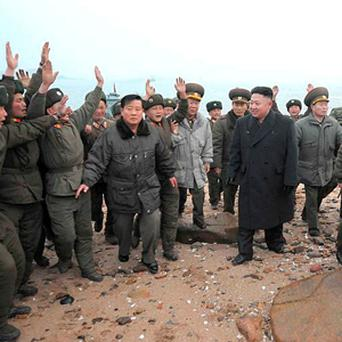 North Korean soldiers greet the North's leader Kim Jong-Un during his visit to the detachments near the border with South Korea.
