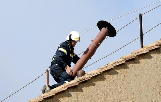 A member of the fire and rescue service sets a chimney on the roof of the Sistine Chapel