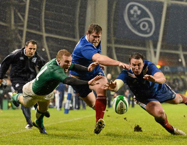 Keith Earls tussles with Vincent Debaty, left, as Louis Picamoles, France, gains possession by the try line. Photo: Sportsfile