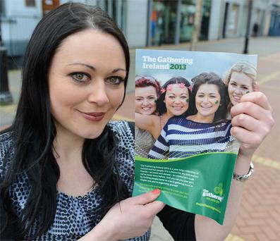 Charlene Carbery holds an ad for The Gathering, where she is pictured second from left