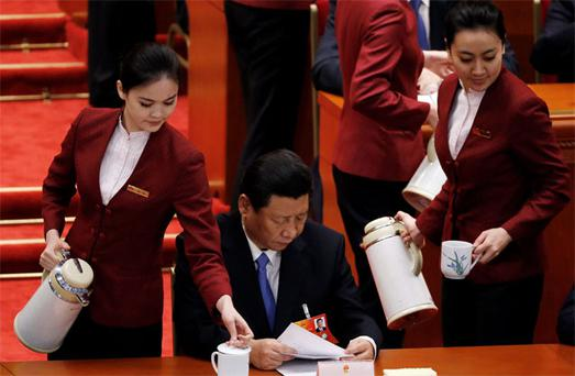 Communist Party Chief Xi Jinping reads as attendants serve tea at the Great Hall of the People during a session of the National People's Congress in Beijing yesterday
