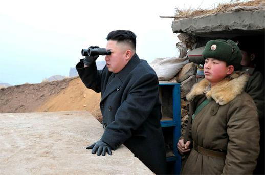 Kim Jong-Un (C) uses a pair of binoculars to look towards the South during his visit to the Jangjae Islet Defence Detachment