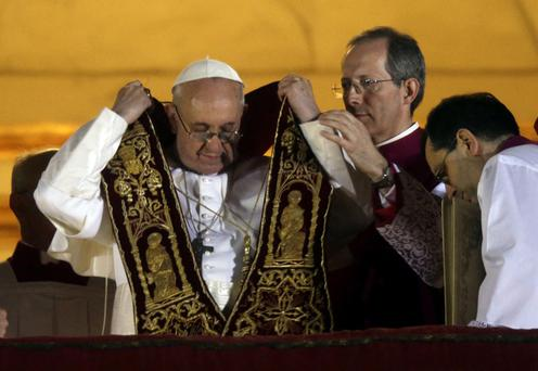 Pope Francis puts on his sash from the central balcony of St. Peter's Basilica at the Vatican