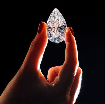 A Christie's employee holds a 101.73 carat pear-shaped diamond, the largest D colour flawless diamond ever to be offered for sale at auction