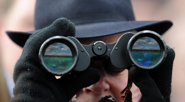 A racegoer watches the action through his binoculars today. Photo: PA