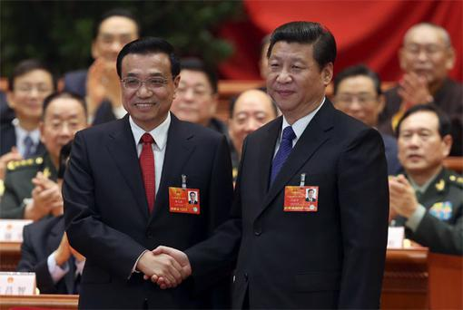 China's newly-elected Premier Li Keqiang (L) shakes hands with China's President Xi Jinping