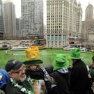 Spectators watch as the Chicago River is dyed green ahead of the St. Patrick's Day parade in Chicago, Saturday, March, 16, 2013.
