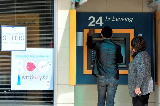 People gather at an automatic teller machine in Nicosia