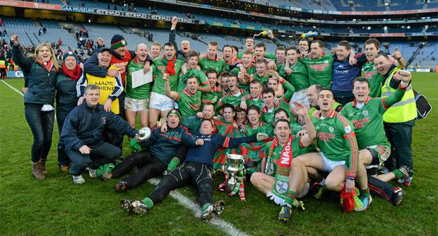 St Brigid's players and officials celebrate with the Andy Merrigan cup