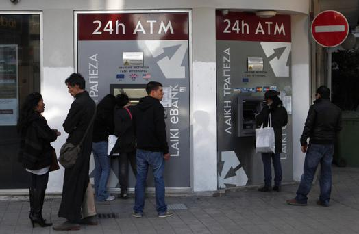 People wait and use the ATM machines outside of a Laiki Bank branch in capital Nicosia, Cyprus
