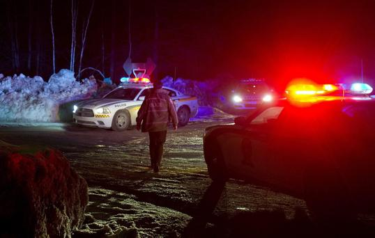 Police vehicles block a road just outside the town of Chertsey, Quebec, during search for escaped prisoners.