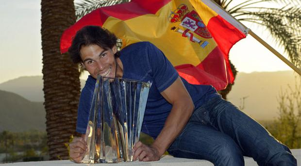 Rafael Nadal poses with the trophy and Spain's flag after defeating Juan Martin del Potro in the final of the BNP Paribas Open