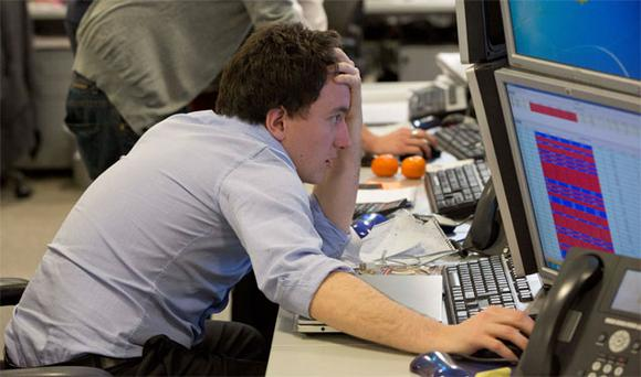 A trader looks at his screen on the IG Group trading floor in London. The surprise decision by euro zone leaders to part-fund a bailout of Cyprus by taxing bank deposits sent shockwaves through financial markets on Monday, with shares and the bonds of struggling euro zone governments tumbling.