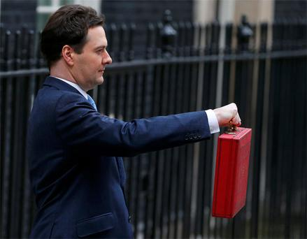 Britain's Chancellor of the Exchequer, George Osborne, holds up his budget case for the cameras as he stands outside number 11 Downing Street, before delivering his budget to the House of Commons