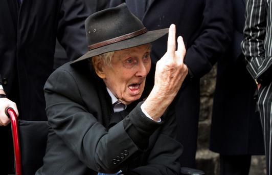 Great Train Robber Ronnie Biggs gestures to photographers at the funeral of Bruce Reynolds, at the church of St Bartholomew the Great in London