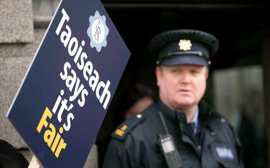 A GRA placard beside an on duty garda during an AGSI/GRA protest over propsed government cutbacks outside Leinster House