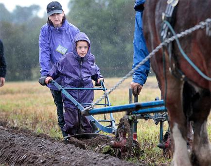 Roisin Lardney (7), from Galway, helping her mum Caroline during the Under 40 Horse Plough Class at last year's National Ploughing Championships at Heathpark near New Ross, Co Wexford