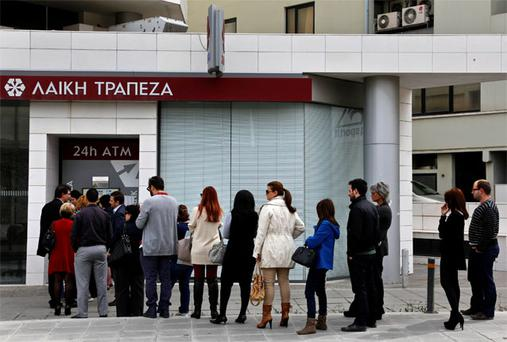 People queue up to make a transaction at an ATM outside a branch of Laiki Bank in Nicosia