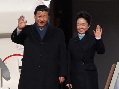 Chinese President Xi Jinping and First Lady Peng Liyuan wave as they disembark from a plane upon their arrival in Moscow