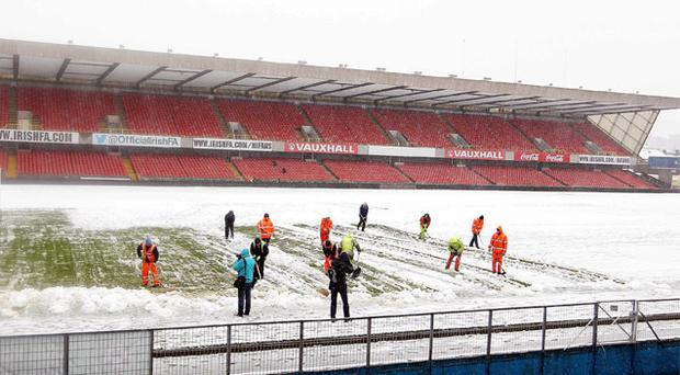 Ground staff help clear snow away from Windsor Park